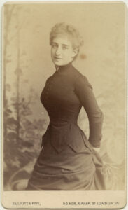 """Ada Leverson is shown standing (or possibly leaning) with hands clasped behind her in a front facing pose, angled slightly to the right. Though her body is angled, she is gazing straightforward. Her eyes appear to be lightly coloured, and she is smiling softly. Her hair is very short, curly, and falls slightly onto her forehead. Leverson is wearing a dark button-up dress. The dress has a collar that extends the length of her neck, decorative pointed fabric that hangs off her waist section, and a skirt that extends outward at her waist and bunches up behind her. In the background, behind Leverson, there appears to be a garden with upward growing vines. The image is shaded in brown sepia tones, and has a beige rounded-rectangular border. The text """"ELLIOTT & FRY 55&56, BAKER ST LONDON, W"""" is written in capitalized letters within the bottom border of the photograph."""
