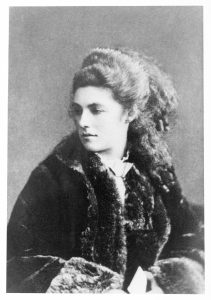 This photograph of Mathilde Blind shows her seated, and is taken from the waist up. Her head is turned slightly to the right, her body angled the left. She is wearing a large fur coat, and her sleeved arms are visible at the bottom of the photograph. She is holding a print object. Her hair is half pinned up, left ear visible, and the ends are curled into small ringlets.