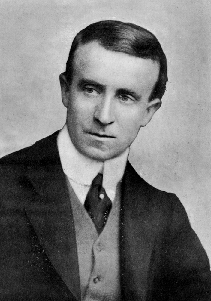 John Buchan is shown from the middle of his chest up, his face turned towards the right, eyes also turned towards the right. He is wearing a suit, vest, tie, and high-collared shirt. The background is light-coloured.