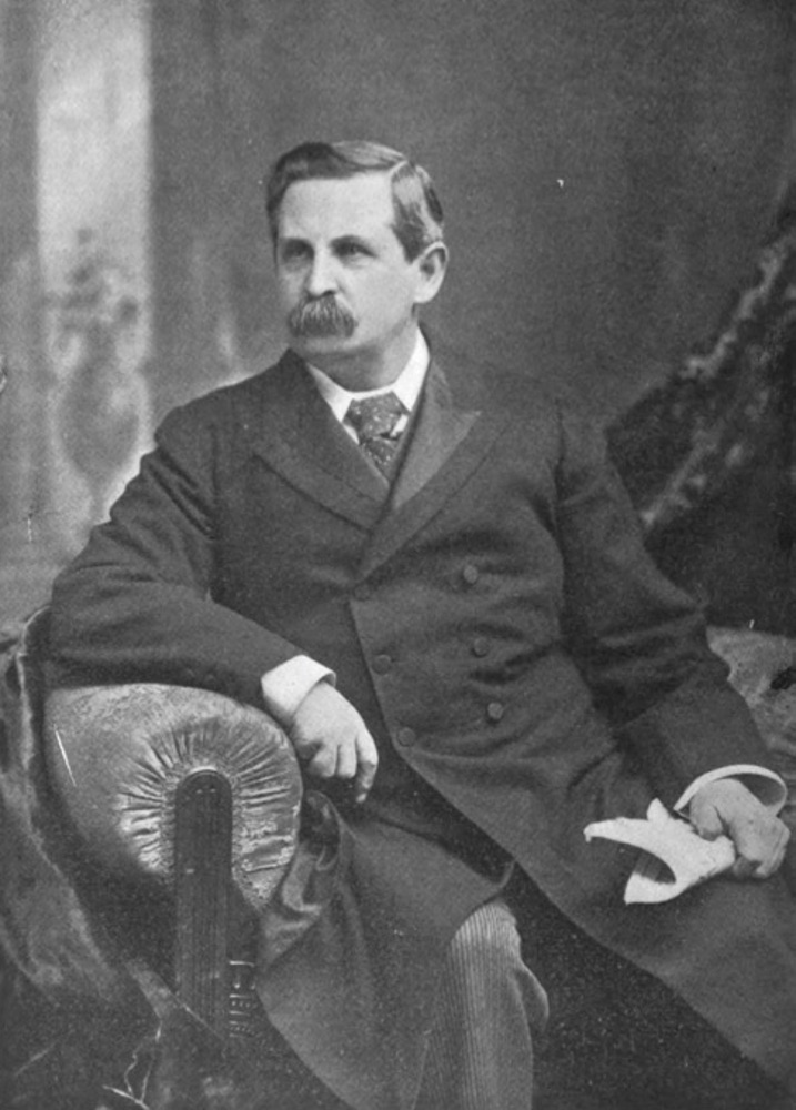 Black-and-white 3/4-photographic image of a moustached man in a long suit-coat and tie. He is seated in a chair, gazing off past the camera's left. His left hand holds a newspaper and his right arm rests on the chair arm. The pose, gaze, and a background panel possibly evoking a classical motif suggests this is a studio portrait.