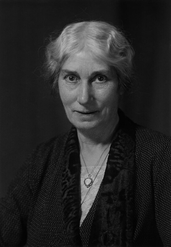 The photograph is in black and white. Evelyn Sharp is shown in a                            head-and-shoulders pose with her body slightly angled towards the left                            of the image. Her gaze is straight on the camera, directed at the                            viewer, and she is slightly smiling. Her hair is grey or white, has a                            softly waved texture, and is tied back, partially covering her ears. She                            is wearing a dark dress with a tiny polka dot print. There is a                            triangular lace cutout at the collar of her shirt, and she is wearing a                            scarf with a velvety texture. She is wearing two necklaces, one has a                            pendant with an upside-down teardrop shaped stone inlaid. The other                            necklace is partially obscured by her scarf, no pendant is                            visible.