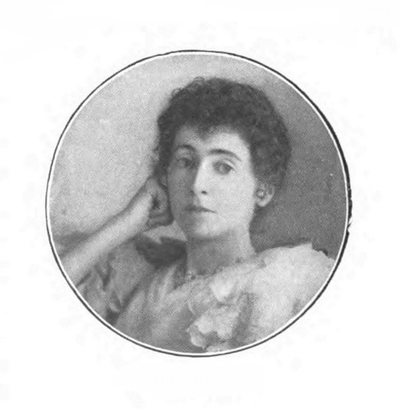 Margaret Louisa Woods is shown in a head-and-shoulders pose. Her body is facing right, but her head and gaze are directed straightforward. Her right arm is bent, and her right hand is making a relaxed fist positioned up against her cheek. Her facial features are illuminated by a light source coming in from the right side of the image, casting a minimal shadow on the left side of her face. She is not smiling, but her eyebrows are slightly raised. Woods' hair is dark, curly, and cut short to frame her face. She is wearing ball-stud earrings and a beaded necklace. She is wearing a ¾ sleeve chiffon dress that is lightly coloured. The photograph is coloured black and white, and positioned within a circular lined frame.