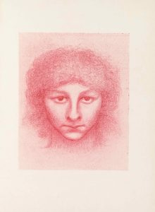"This half-tone reproduction of a crayon drawing printed in red ink is in portrait orientation. The drawing of a head floats in a plain background. The head takes up the whole central area of the image, leaving only a little space on each side and a little more above and below. The head is facing the viewer straight on, with a slight tilt of the chin downwards. The face is round with a slightly squared chin. There is a mouth depicted in a tight line. The nose takes up a large portion of the face, and the eyes are proportionately large as well. The irises are positioned at the top of the eyeball, as a result of the chin being pointed down slightly. The brows angle up towards the sides of the face in a straight line. Frizzy, curly hair falls down on the face in bangs to the mid-forehead and temples. The hair also falls around the sides of the face, creating a puffy cushioning of hair around the head. There is brief shading below the chin to indicate the start of a neck. The image is drawn in a burnt orange-red colour (""sanguine"") on a pale background."