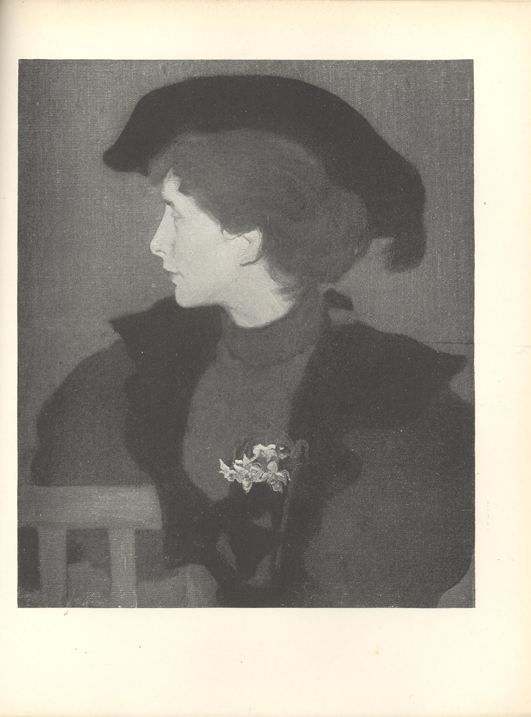 Image is the torso of a seated woman wearing a black hat with feather She is dressed in outside clothes with a white corsage in the lapel of her cloak She is sitting on a chair that s facing frontward with her head turned in profile to the left Her shoulders divide the pictorial space in half horizontally The chair is in the bottom left hand corner of the frame The background is open and dark coloured The image is vertically displayed.