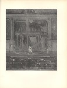 Image is of a music hall viewed from the back of the theatre. The stage divides the frame into three sections The central and largest section is the performance area where a small blonde woman wearing a short white dress is standing on a proscenium stage The theatrical facade behind the woman contains many curtains and lights The upper section at the extreme top of the image is of some moulding over centre stage The lower section of the image is comprised of several rows of audience members the orchestra pit and the conductor The image is vertically displayed