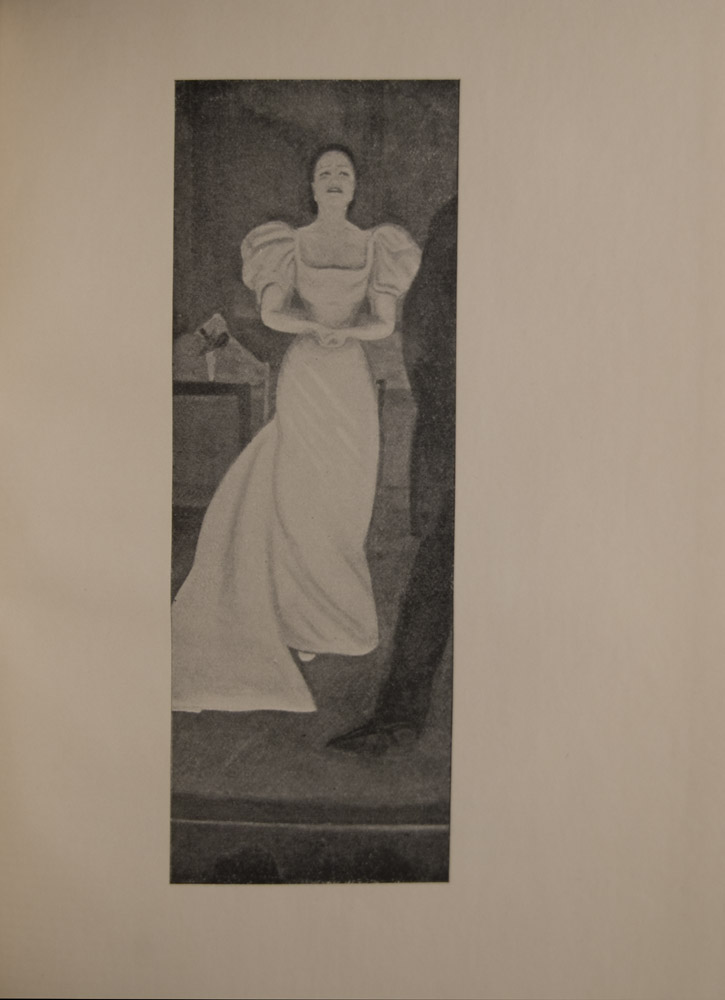 The image is of a woman standing on a stage She wears a long white dress with a train and is standing with hands clasped Her hair is pulled back and her face shows emotion she may be singing or weeping The back leg and left arm of a man stands in front just to the right of her He wears a dark suit At the bottom of the frame there is the suggestion of men s hats below edge of stage There are indistinguishable objects in the background on stage The image is vertically displayed