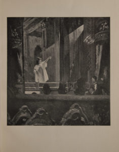 The image is of a small female figure on a stage in a white gown pointing upwards to a balcony She is illuminated by a wide beam of light coming from behind curtain at right There are rounded balconies on either side of the stage In the foreground at the bottom of the image there is a row of chairs with their backs facing the viewer Above the chairs in the middle ground there are the backs of audience members The image is displayed vertically