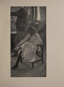 The image is of a seated girl or young woman putting on her shoe in the foreground her hair is over her face and she wears a light white dress or under dress Behind her stands a man his full length figure is in profile The man s head is cut off and out of frame The scene is an interior room with a window behind the man s back There are tables beside and behind him The man is in trousers and dark jacket with a white collar The image is displayed vertically