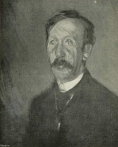 The image is of a mans head and shoulders The man is facing very slightly to the left and his gaze follows the direction he is facing He has dark hair which is parted on the left side of his head The man also has a dark moustache He wears a white collar with a dark jacket The image is vertically displayed