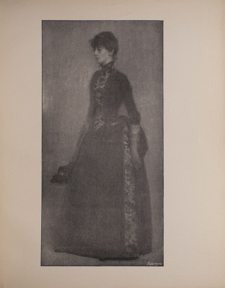 The image is of a woman standing and turned to the left She is wearing a dark coloured dress with a panel of pattern running vertically along the front of the bodice and the side of the skirt of the dress The image is vertically displayed