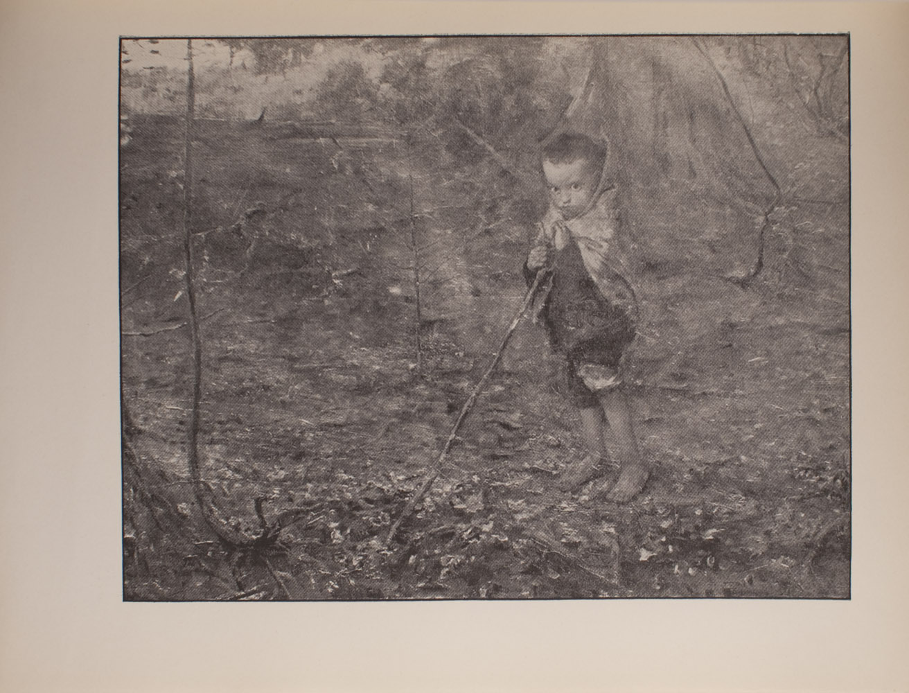 The image is of a young boy in a wooded area The boy stands barefoot holding a long stick that extends diagonally to the left He is wearing pants which are rolled up to his knees and appears to have a scarf or blanket wrapped around his shoulders and the back of his head The boy faces the viewer The image is horizontally displayed