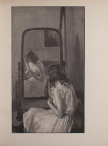 The image is of a female figure who is seated in front of a freestanding mirror Her back is to the viewer but her face is visible through the reflection in the mirror The woman is wearing a sleeveless white dressing gown with a ruffled neckline and black stockings and shoes Her hands rest together in front of her chest and her gaze is cast downwards In the mirrors reflection there is a painting that hangs on the wall behind the woman The image is vertically displayed