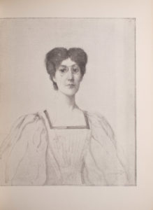 The image is of a woman with dark hair and pince-nez glasses It is a half-portrait and only her upper body is visible She is wearing her hair up parted in the middle She is facing front The woman is wearing clothing with a square neckline and billowy sleeves The neckline has a dark border The image is vertically displayed