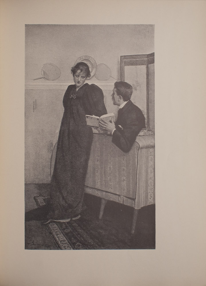 The image is of a seated man showing a standing woman a page from The Yellow Book appears to be Volume III The man is to the right of the woman slightly leaning over the back of a couch with The Yellow Book open The man is in profile and looking towards the woman He has a moustache and is wearing a suit jacket with a collared shirt and a pocket square The woman is leaning against the back of the couch Her hair is done up and she is wearing a long dark coloured dress with large sleeves She is looking at the open page of The Yellow Book The couch and woman both stand on a patterned rug In the background there is a shelf or mantel with a decorative plate and two fans To the right of the shelf or mantel is what appears to be a dressing screen The image is vertically displayed