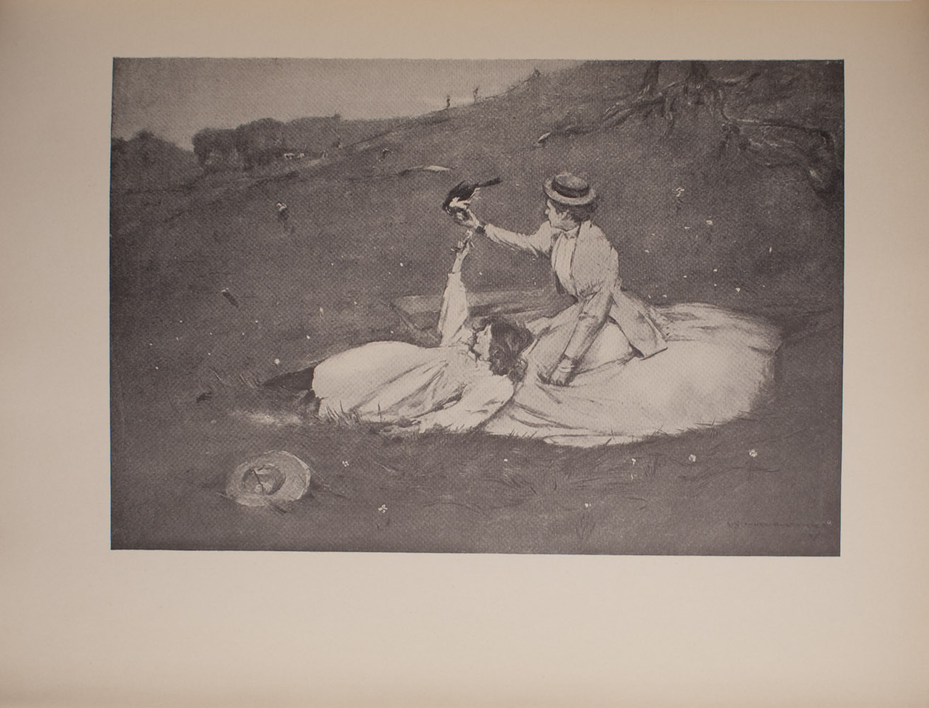 The image is of two women on a hillside One of the women is seated and wears a light coloured skirt with a light coloured jacket Her skirt is spread around her She is wearing a hat and her head is slightly turned away from the viewer Her right arm is extended and a black bird is resting on her fingers The other woman is to the left of the seated woman She is reclined and resting against the seated woman She is wearing a light coloured dress and her hair is down Her right arm is extended towards the black bird She is in profile and smiling Next to the reclining woman further in the foreground is a hat Beyond the two women large tree roots are visible In the background there are more trees and hills Two figures are visible climbing up the hill in the far background There are light coloured flowers around the women The image is horizontally displayed