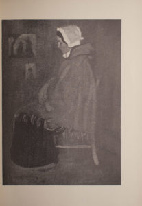 The image is of a seated woman in profile facing left The woman is wearing a light coloured bonnet a dark skirt and a large shawl wrapped around her shoulders She is sitting on a chair and only the legs are visible Her gaze is slightly downcast In the background there appears to be two pictures on the wall to the left of the seated woman The image is vertically displayed
