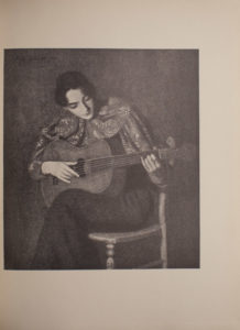 The image is of a seated woman playing an acoustic guitar The woman has dark hair and her gaze is cast downwards and to the right towards the guitar in her lap Her left hand is on the fret board while her right hand plucks the strings She is wearing a patterned top with a large collar and appears to be sitting with her legs crossed The image is vertically displayed