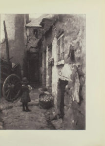 Image is of an alleyway There is child standing in a cobblestone street shown from behind The child is holding onto an unidentified object bread and is wearing dark coloured dress shoes and stockings To the left of the child is a wagon to the right is a bushel basket of apples or potatoes leaning against the white wall of a building A bunch of flowers hangs above the bushel on the wall To the right of these flowers at the same level as the other doors is a window with a white frame There are several doors in this wall The wall divides the image in half vertically A pair of shoes sits on a step between two doors In the middle of the image there is a shadowed doorway; directly above this doorway is an open two framed window A child figure has its arms draped over the sill an adult figure is standing behind the child The artists signature Stanhope A Forbes is in the lower left hand corner The image is vertically displayed