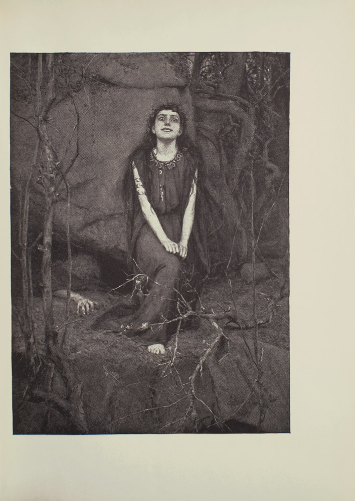 Image is of a woman in a forest She is sitting in the centre of the image her face looking forward Her hands are curled up and resting on her right knee which extends away from her body A crown of leaves is sitting atop the womans long dark hair She is wearing a long sleeveless dark coloured dress with a decorated neckline The top of her right foot is poking out from beneath the dress slightly more than the toes are all that is visible A wraparound golden armlet is around her right upper arm She is shown in full face tilted slightly upward with wide almost demented eyes and a mysterious smile She is sitting in front of a large rock A persons arm is emerging from under the rock their fingers grasping at the ground The figures body is faint seen in the darkness of a large crevice Large roots and small trees branches surround the image The image is vertically displayed