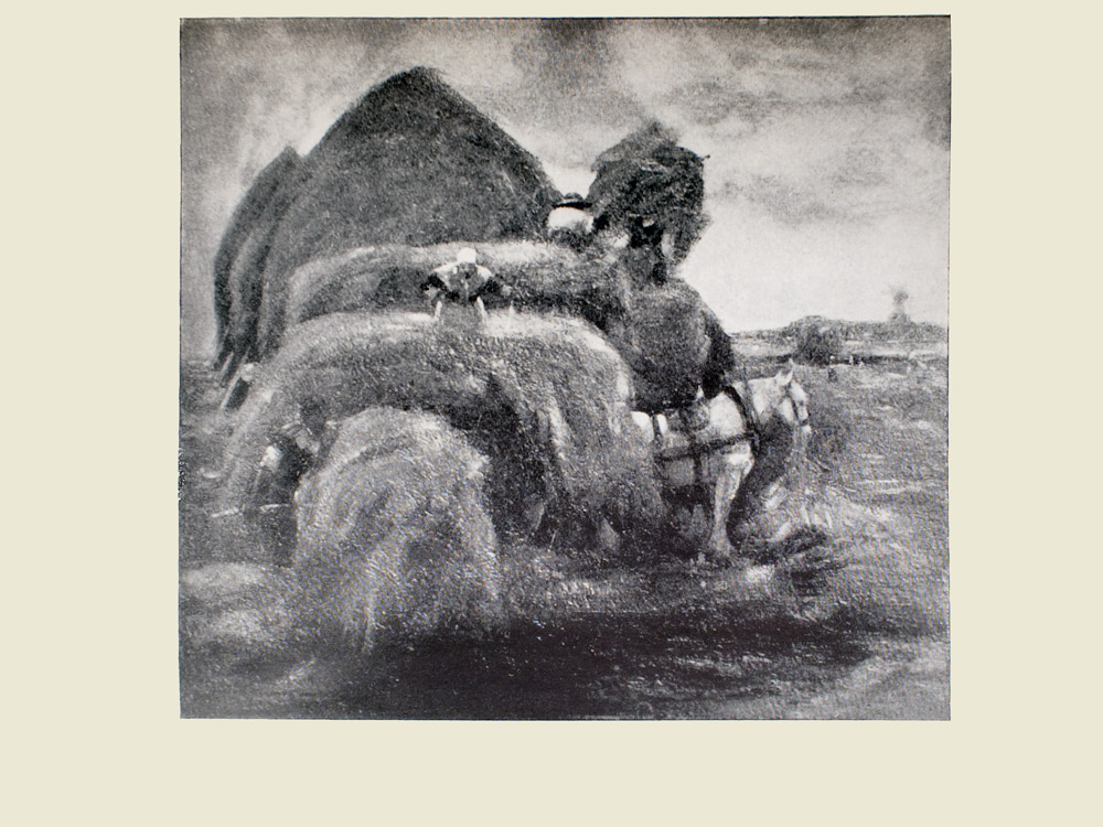 Image is of a woman stacking hay onto a wagon She the horse and the wagon are in the middle ground The horse is white and is shown in profile facing the right of the image The woman is wearing a light coloured bonnet Behind the woman is a larger stack of hay a figure shown from the back is on top of it In behind this larger stack are three buildings with straw roofs The sky is light coloured The image is horizontally displayed