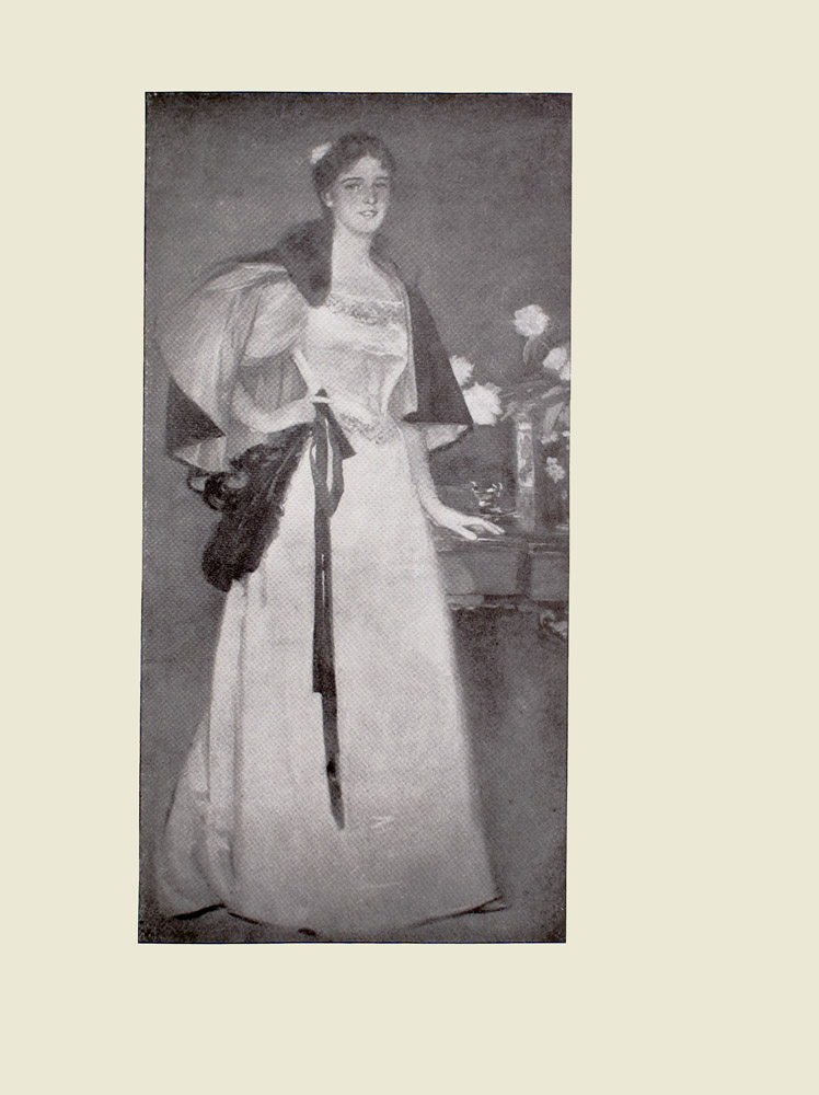 Image is of a woman shown full frontally Her teeth are visible through her slightly parted teeth She is wearing a long detailed gown that reaches the floor Only her left foot can be seen it sticks out slightly from underneath her dress Her hair is tied back The a line dress has a fitted bodice She is wearing a short dark cape part of the cape is draped around her chest. The womans right hand is holding on to a dark coloured ribbon and a dark feather her left hand is resting on a table The table divides the image horizontally The table has a vase of white flowers and a teacup and saucer The background is dark and undefined The image is vertically displayed
