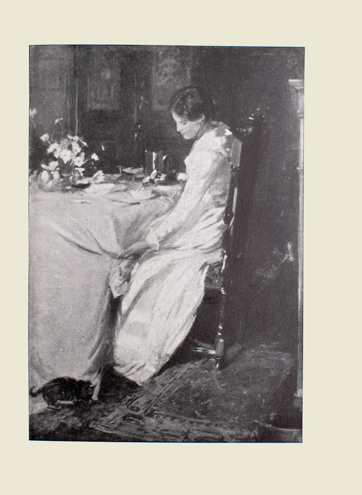 Image is of a woman sitting at a table in a dining room She is shown in profile, facing the left Her body divides the image in half vertically The woman is wearing a long white dress that reaches the floor Her dark hair is tied back She is sitting in a tall dark chair that is only slightly shorter than her frame Her left hand is reaching down towards the ground where a small dark cat is sniffing the bottom of the white tablecloth Under the chair is a detailed Persian rug On the table are place settings and a vase of white daisies Behind the woman is the white mantel of a fireplace In the bottom right hand corner there is a brass pot In the background the faint outline of cabinets can be seen The image is vertically displayed