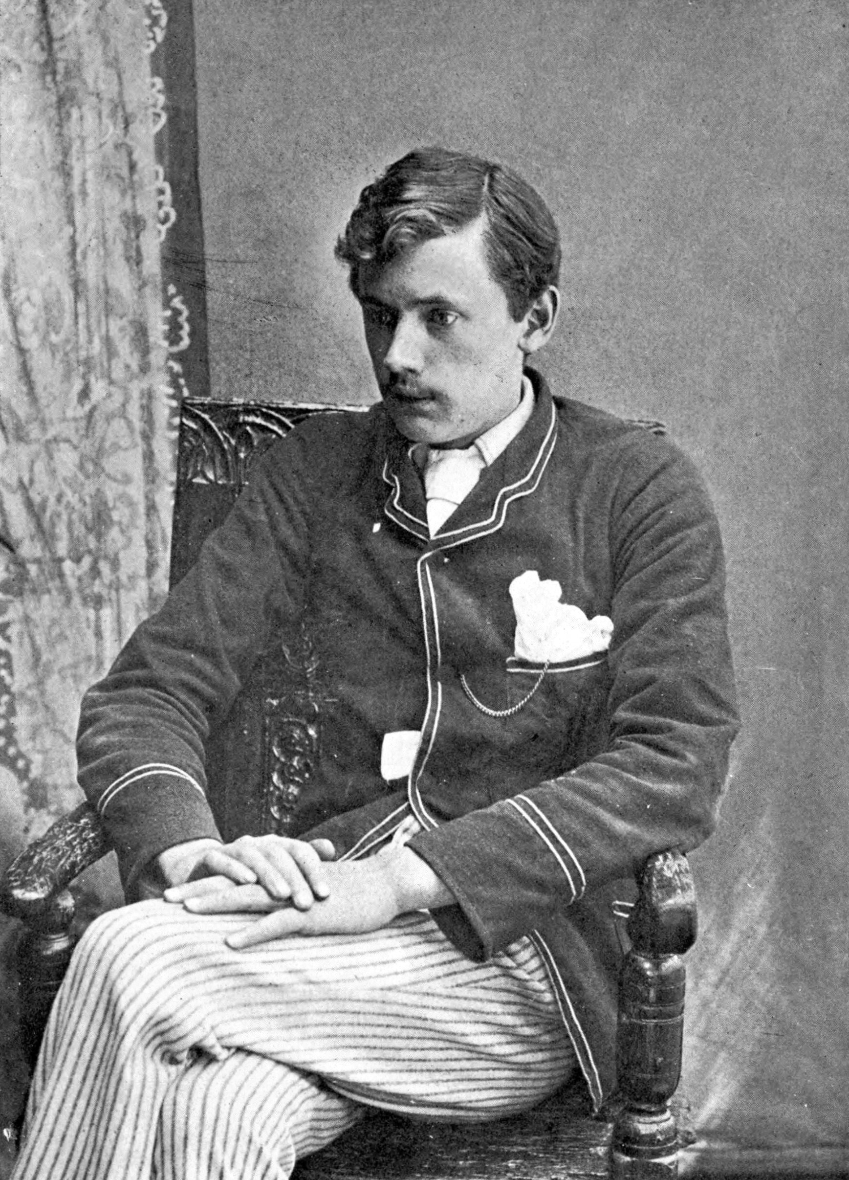Black-and-white image of Ernest Dowson sitting in a chair with his left leg crossed over his right and his hands lying on his top knee. He is wearing informal dress: a dark cardigan-suit jacket and white pinstriped pants, with a white fabric in his breast pocket. His gaze is down and towards his right.