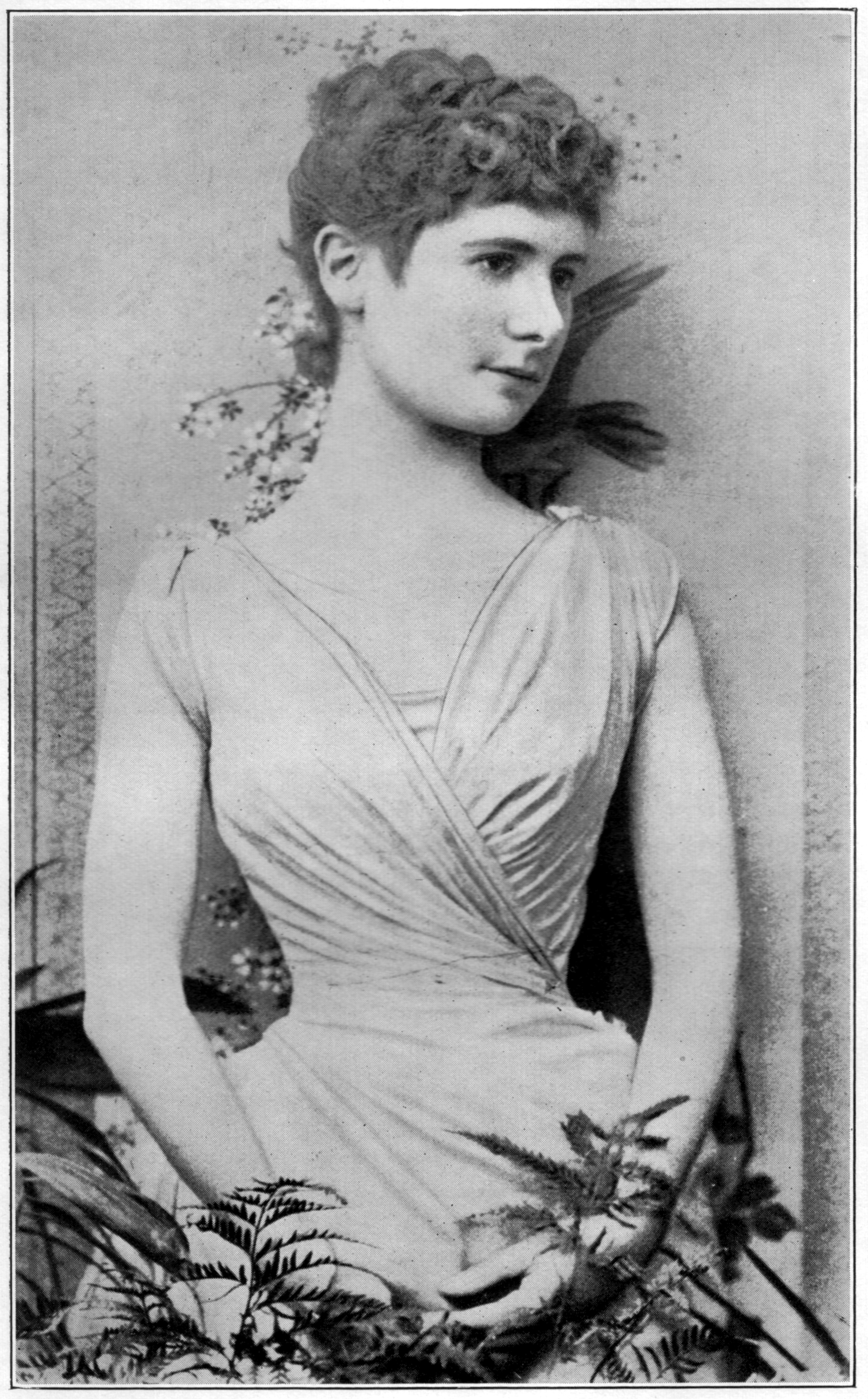 The young Ella Hepworth Dixon is photographed in ¾ view. She is wearing an evening dress and posed behind potted plants.