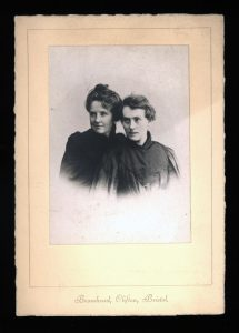 """This photograph of Katherine Bradley and Edith Cooper is taken from the chest up fading out around the mid-chest area. Both women are positioned with their bodies angled slightly to the right, and are looking towards the left side of the photograph. Katherine is in the front, wearing a high-necked dress with a cape or jacket hanging on her shoulders. Her hair is short, covering the tops of her ears. It's parted on the right side of her head, and is swept back. Edith is also wearing a high-necked dress, details are obscured in shadow. Her hair is up in a bun. Both women are slightly smiling. The photo is on a plain card, which reads """"Bromhead, Clifton, Bristol"""" in cursive typeface at the bottom."""