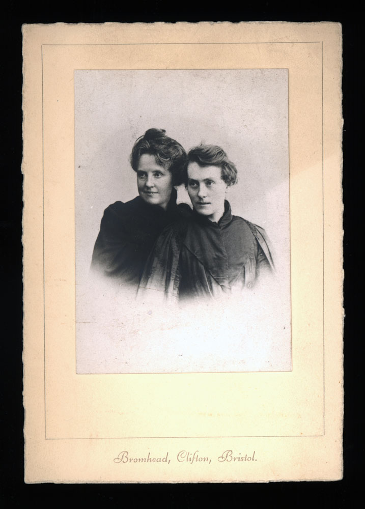 "This photograph of Katherine Bradley and Edith Cooper is taken from the chest up fading out around the mid-chest area. Both women are positioned with their bodies angled slightly to the right, and are looking towards the left side of the photograph. Katherine is in the front, wearing a high-necked dress with a cape or jacket hanging on her shoulders. Her hair is short, covering the tops of her ears. It's parted on the right side of her head, and is swept back. Edith is also wearing a high-necked dress, details are obscured in shadow. Her hair is up in a bun. Both women are slightly smiling. The photo is on a plain card, which reads ""Bromhead, Clifton, Bristol"" in cursive typeface at the bottom."