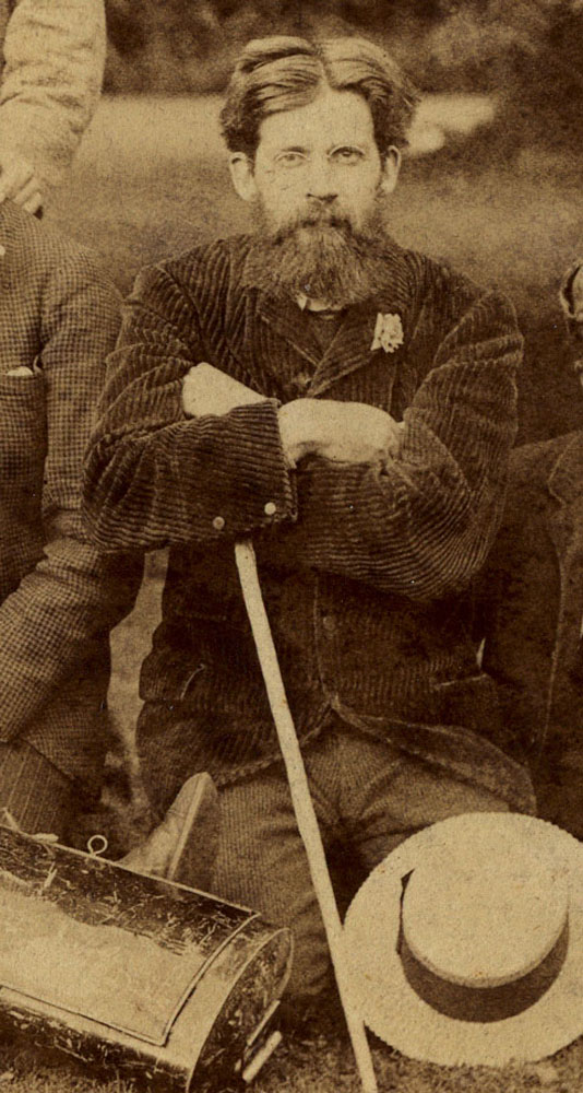 Sepia-tone image is of Patrick Geddes on a field study, kneeling on the ground. His arms are crossed and his gaze is directly on the viewer. He is wearing a dark corduroy suit jacket and lighter pants. He is holding a white stick in one hand; possibly a walking stick. A circular-brimmed light hair lies on the ground, covering his left knee and thigh.