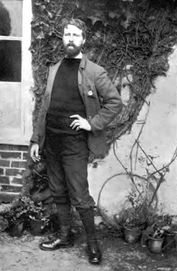 This photograph of Thomas Cooper Gotch is full-length and shows him standing outside of a building, facing the camera with his left hand on his hip, right hand hanging loosely. His left foot points forwards, and right foot points left. He is wearing a sweater, trousers, and jacket; the left side of his jacket rests behind his left arm. A light handkerchief is sticking out of the left breast pocket. He has a full beard, and his hair is cut short, about 2 inches long. One piece of hair has been swept onto his forehead. The photograph was taken beside a building, in the background the brick wall, a large ivy vine and window are visible. Potted plants are on the ground behind him, on either side of him.
