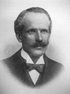 Carl Hentschel is wearing a dress suit with bow tie. He is gazing camera right viewed in close-up from his shoulders and above. The photograph is in black and white.