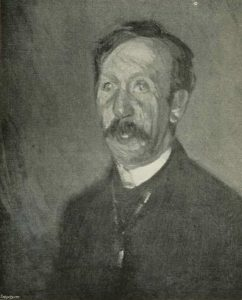 The image is of a man's head and shoulders. The man is facing very slightly to the left and his gaze follows the direction he is facing. He has dark hair parted on the left side of his head. The man also has a dark moustache. He wears a white collar with a dark jacket. The image is vertically displayed.