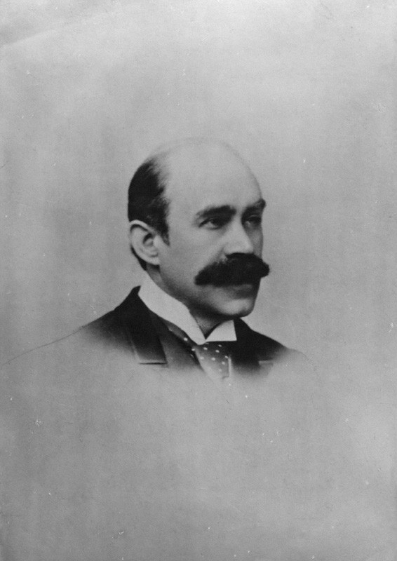This is a photograph of Walter Pater from the shoulders up, in a ¾ pose facing the right side of the image. He is wearing a high collared shirt, wide polka-dot tie, and a dark jacket. The image fades from the top of the tie downwards.