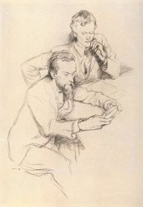 The image is of two men seated at a table. The man on the left is Charles Ricketts and behind him and slightly to the right is Charles Shannon. Ricketts is holding something in both his hands and his gaze is towards this object. Shannon is also looking towards the object in Ricketts' hands. Shannon's chin is resting on his left hand and his left elbow rests on the table. His right arm is bent and partially obstructed by Ricketts. Shannon is wearing a suit jacket with a collared shirt and tie. Rickets also wears a suit and tie and has a moustache and a beard. The image is vertically displayed.