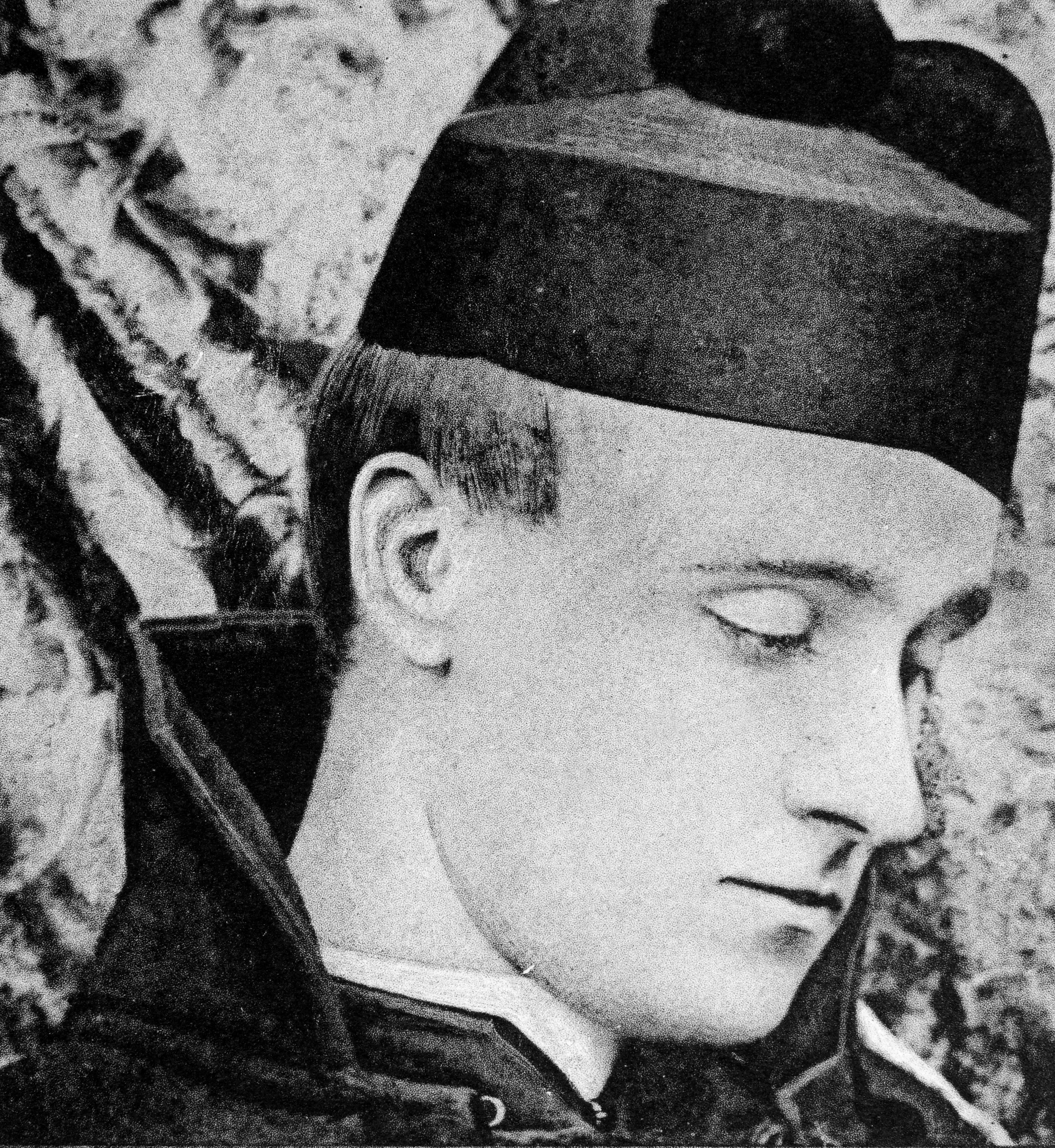 Black-and-white image is a close headshot of Frederick Rolfe, also known as Baron Corvo. He is turned to his left and his gaze is downward and to the left. He is wearing a high-collared jacket and a black hat.