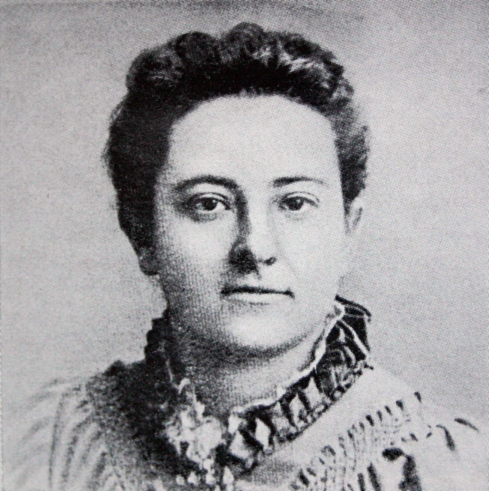 Black-and-white headshot of Olive Schreiner shows her from the shoulders up and facing the camera. Her eyes are gazing very slightly to her left. She is wearing a light-coloured dress or shirt with a dark-coloured, high, ruffled collar.