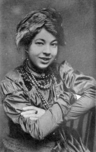 Pamela Colman Smith is shown seated, from the waist up. One arm rests on the back of a wooden chair, and both are crossed in front. Her mouth is open in a smile, and her hair is in an updo with an ornament pinned to the side. She is wearing 4 beaded necklaces of varying lengths and colours, and a ring on her left middle finger. Her dress is embroidered in the collar area, and has puffed sleeves that tighten from the elbows to the wrists.