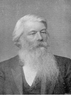Joseph Swan is photographed in frame from the mid-torso. He is wearing a three-piece suit. His head and gaze are turned camera right.