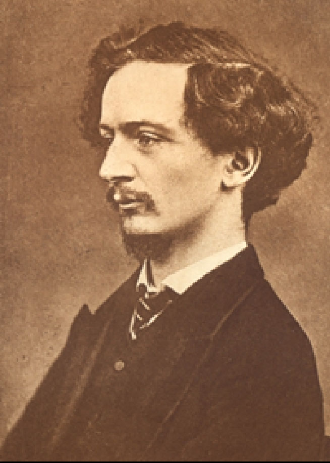 Image is a photograph of Algernon Charles Swinburne shown from the shoulders up. He is wearing a dark suit jacket, a white shirt and a striped tie. He is shown in profile looking to the left. His hair is wavy and parted on the right side. He has a moustache. The background is dark and undefined. The image is vertically displayed.