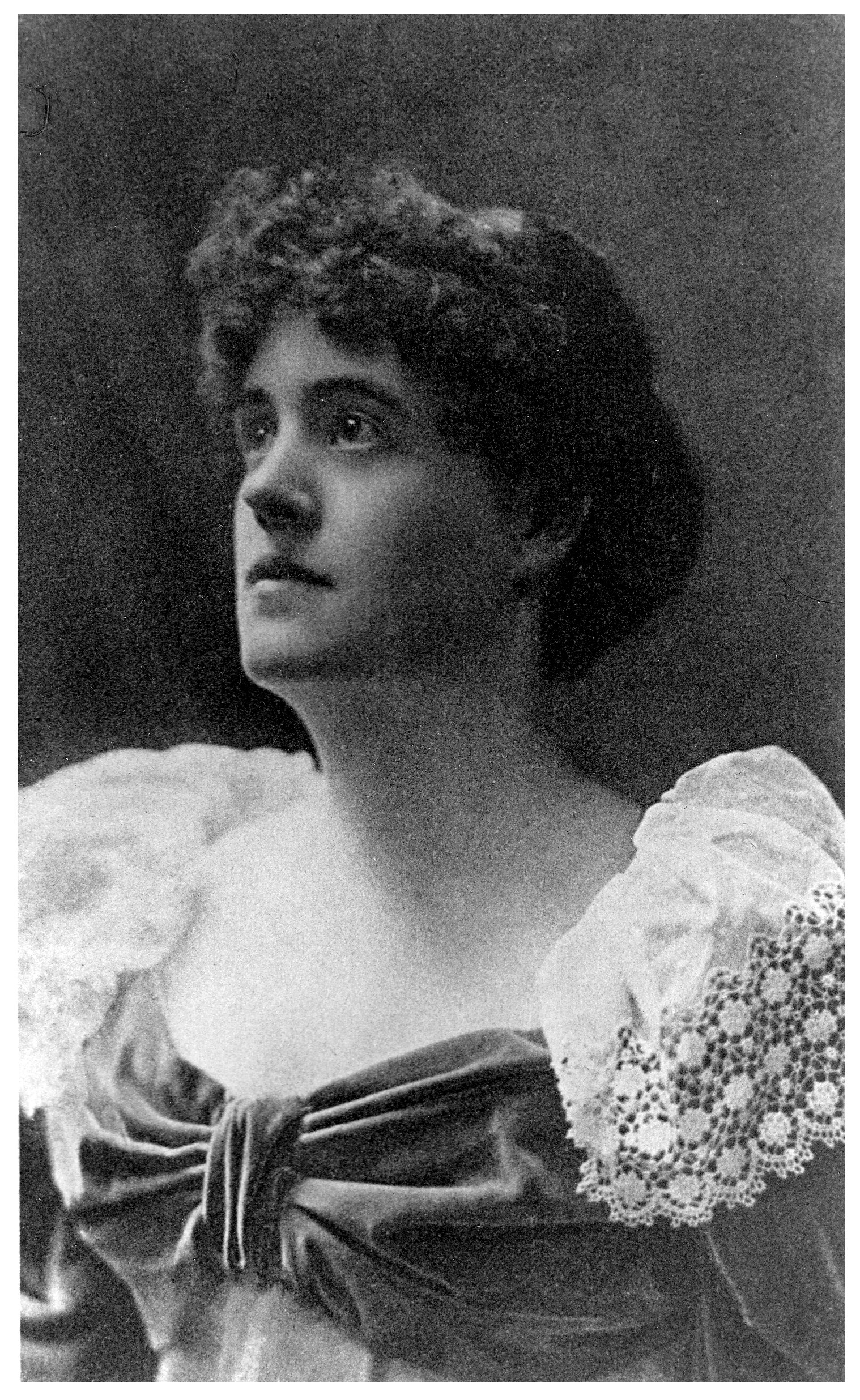 Image is a photograph of Graham Tomson [Rosamund Marriott Watson] shown from the chest up. She is in ¾ face, looking towards the upper left corner of the image. She has curly hair that is worn short. She is wearing a dress with a low neckline; the fabric gathers in a bow in the middle of her chest. The dress has long sleeves accentuated with white lace shoulders. The background is open and dark-coloured. The image is vertically displayed.