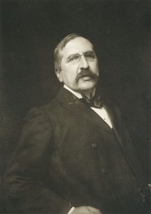 Gleeson White is shown facing forwards from the waist up. He is looking straight ahead. He is wearing a dark double breasted suit, a white collared shirt and a black satin bow tie. His right hand appears to be resting at his side with his elbow slightly bent. His hair is combed to the right side and he is sporting a handlebar moustache and metal rimmed 'pince nez' spectacles.