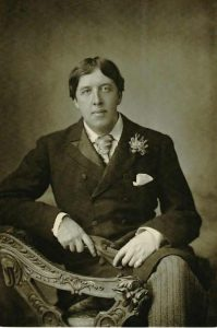 A young Oscar Wilde sits sideways facing the camera on an ornate bench. His left leg is crossed over his right. He is leaning his right elbow on the back of the bench and holding a pair of gloves between both hands. He is wearing pin-striped pants and a long jacket buttoned to the top with a tie visible underneath. There is a white kerchief tucked into his left breast pocket and a flower pinned to his left lapel.