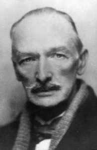 The photograph shows Wilson almost full faced. He sports a moustache that covers his upper lip. He is wearing a scarf and coat and a bowtie is visible. The photograph is soft focused.